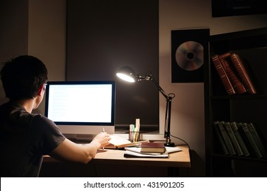 Back view of concentrared asian young man working with blank screen computer in dark room