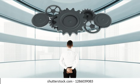 Back view concept of businessman looking at mechanism of cogwheels in modern office