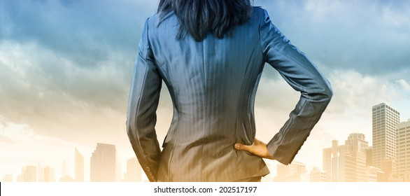 Back view of confident businesswoman with arm on waist