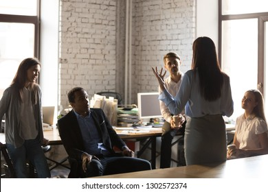 Back view of confident businesswoman standing in front of colleagues, gesturing talking about business ideas or projects, female team leader hold briefing or informational meeting with employees