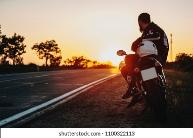 Back view of a confident caucasian biker sitting on his motorcycle resting near the round and looking at the sunset in his adventure on two wheels.