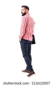 Back view of confident handsome young bearded man holding laptop and walking away. Full body isolated on white background.
