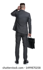 back view of a confused businessman holding briefcase and scratching his head, isolated on white background