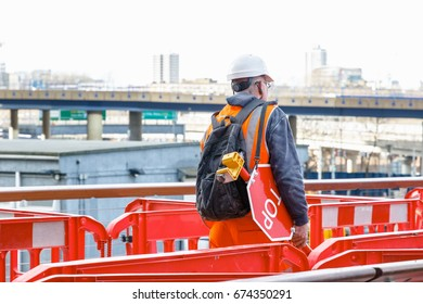Back view of a construction worker with a stop waning sign in a building site in Canary Wharf, London