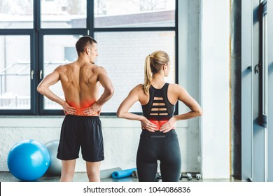 back view of couple having backache after workout in gym