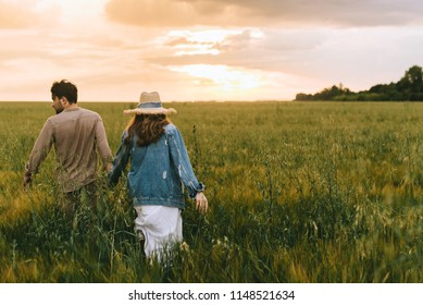 back view of couple holding hands and walking on green meadow at sunset