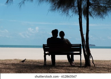 Back view of a couple silhouette hugging and watching the beach