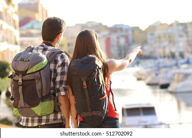 Back view of a couple of tourists sightseeing in a travel destination with a port with colorful buildings in the background