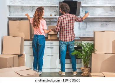 back view of couple unpacking cardboard boxes at new home and putting utensil on shelves