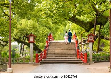 Back view of a couple walking on the bridge. Arched bridge  and  historic shrine, Red bridge in Dazaifu Tenman-gu, Fukuoka, Kyushu, Japan.