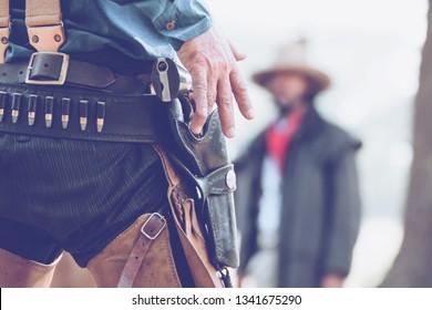 back view of cowboy with gun prepares to gun fight.Conwboy with gun.