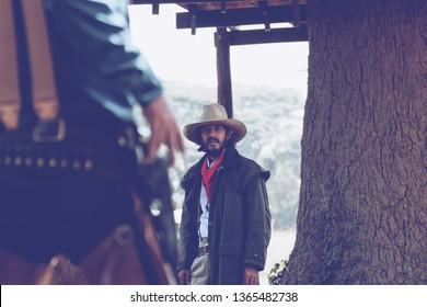 back view of cowboy with gun prepares to gunfight.conwboy with gun.