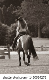 Back view of cowgirl riding a horse in black and white sepia tone woman with long hair and cowboy hat in grass wooden fence at a western ranch