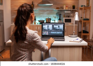 Back view of creative filmmaker working on a movie on laptop during midnight. Content creator in home working on montage of film using modern software for editing late at night.