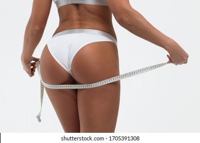 Back view of crop alluring young female in white panties measuring body parts of roulette in studio on white background