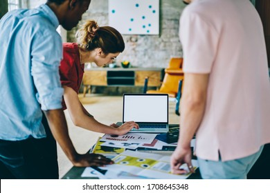 Back view of crop multiethnic male and female employees in casual clothing standing and making business proposal together with blank screen laptop at stylish office