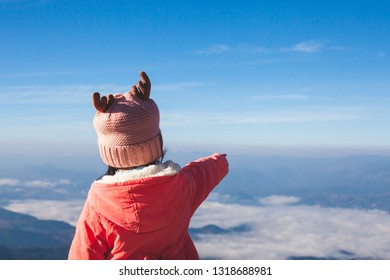 Back view of cute asian child girl wearing sweater and warm hat raise her arm and pointing to beautiful nature in winter