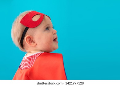 Back view of cute baby in superhero mask and cape looking away against blue background