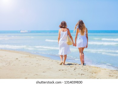Back view of Cute beautiful girl and her mother have a good time at the seaside resort