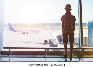 Back view of Cute boy looking at planes in the airport