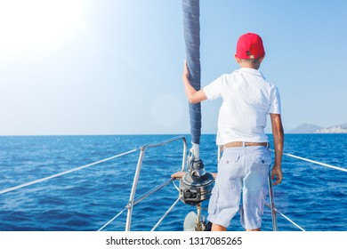 Back view of Cute boy on board of sailing yacht on summer cruise. Travel adventure, yachting with child on family vacation. Kid clothing in sailor style, nautical fashion.
