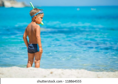 Back view of cute boy snorkelling ready swimming in the transparent sea
