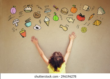back view of cute kid imagine various foods with set of infographics over textured wall background