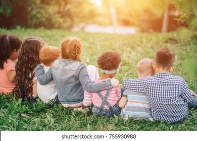 Back view of cute kids seated on green grass and relaxing. Outdoors. The concept of childhood and friendship.
