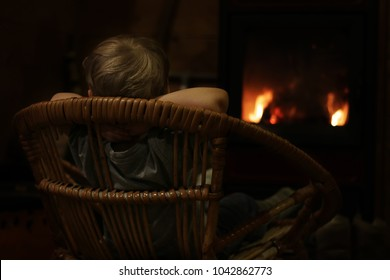 Back view of a cute little 3 years old boy sitting on the twigged armchair and dreaming near burning fireplace, indoor portrait, cozy interior and mood