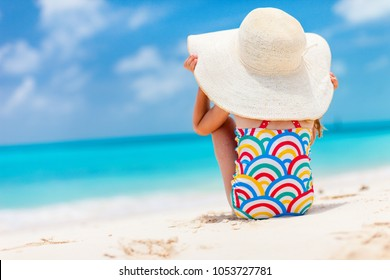 Back view of a cute little girl in a big straw hat at tropical beach