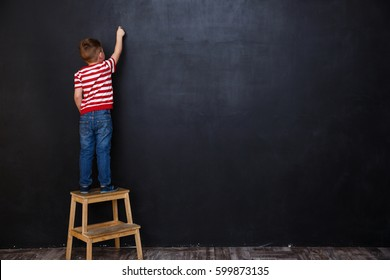 Back view of cute little kid boy standing on ladder and writing with chalk on the backboard in school class