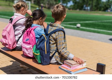 back view of cute little schoolkids with books sitting together on bench