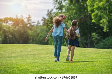 Back view of cute multiethnic girls walking together in park