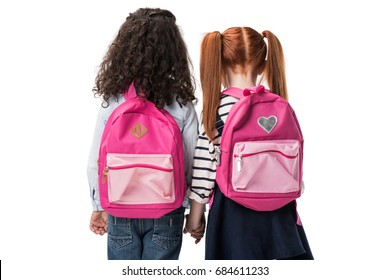 back view of cute multiethnic schoolgirls with backpacks standing together isolated on white