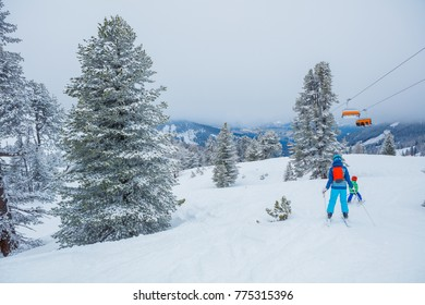 Back view of cute skier kids in a winter ski resort.