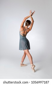 Back view of a dancer wearing a crossed open back gray leotard