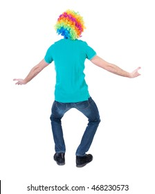 back view of dancing young beautiful  man  in clown wig.  Rear view people collection.  backside view of person.  Isolated over white background. Curly man in a turquoise sweater and clown wig squats.