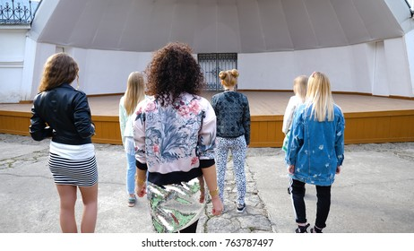 Back view of dancing young women. Girls dance, enjoy and express positive emotions and having fun on outdoor. Group of beautiful girls participating in the flashmob
