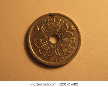 Back view of Danish coin. 1 krone from Denmark. Great for numismatic collection. Shiny coin from Danmark isolated on yellow surface of paper.