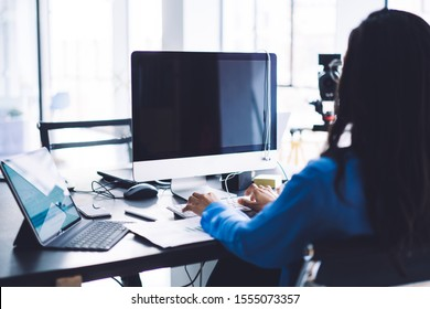 Back view of dark haired woman turned to large black monitor starting using desktop after working with laptop and documents