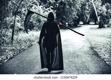 Back view of demon witch with reaper and red blood on hands walking along moon light road background. Horror and Ghost concept. Halloween day and Scary scene theme. Killer and moonlight death theme.