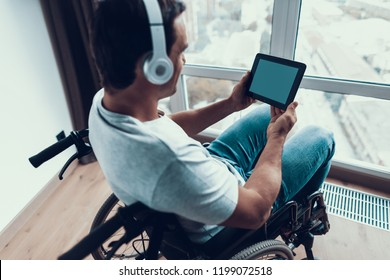 Back View Disabled Man in Headphones Uses Tablet. Closeup of Handsome Happy Person in Casual Clothes Sits in Modern Wheelchair Parked near Window in Living Room or Hospital. Man Watch at Empty Screen