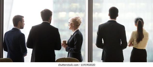 Back view of diverse colleagues stand near big windows talking discussing projects, office employees enjoy coffee break looking in distance, having business conversation, workers chatting at meeting