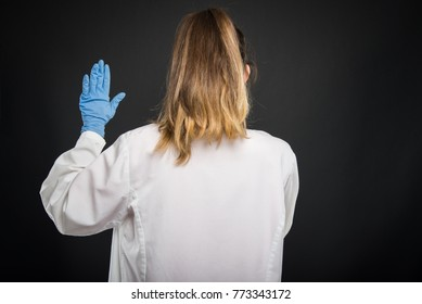Back view of doctor wearing robe taking Hippocratic oath on black background with copyspace advertising area