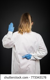 Back view of doctor wearing robe taking fake Hippocratic oath with fingers crossed on black background