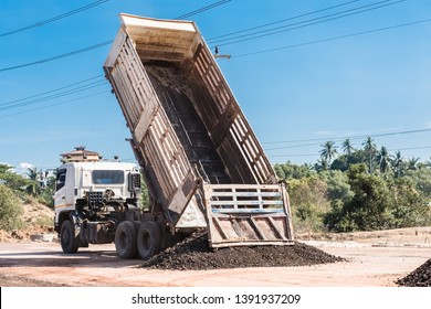 Back view of dump truck unloading soil or sand at construction site with blue sky.