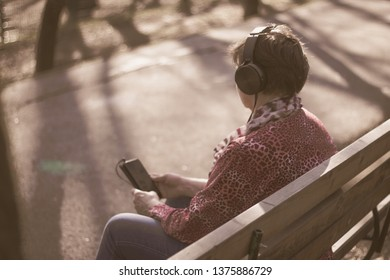 Back view of an elder lady listening to music on her headphones sitting on a bench in the park – Senior woman shot from behind using the phone – Concept of old people using technology