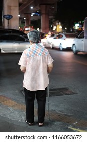Back view of elderly Asian women try to cross the road. Lonely Asia old lady standing on footpath in the night time. blur many car and bad traffic background. Concept elder day, Take care of elderly.