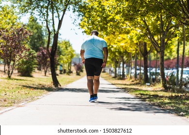 Back view of an elderly black and African-American man with overweight problems running in the park in the city