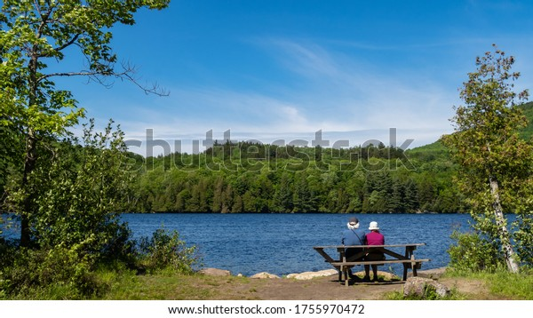 Back view of an elderly couple sitting in front of Lake Stukely, at the mont-Orford national park, Canada
